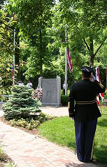 Soldier saluting to flag and memorial area at Veterans Memorial Park